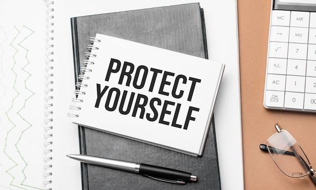 Proteggetevi sul blocco note e vari documenti aziendali su sfondo marrone.
