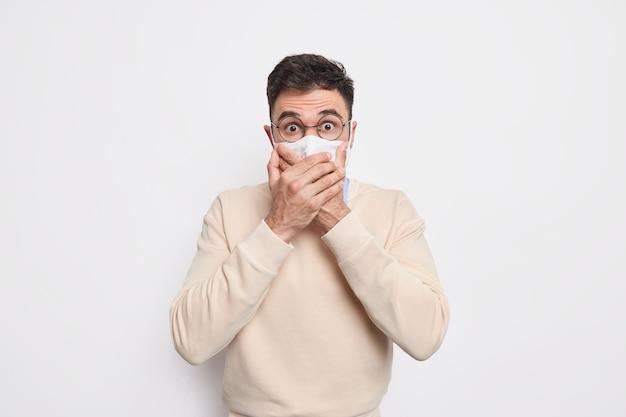 Protezione contro le malattie. l'uomo spaventato e scioccato tiene le mani sulla bocca indossa una maschera protettiva per prevenire il coronavirus o le pose di malattie contagiose contro il muro bianco stordito dalla nuova realtà