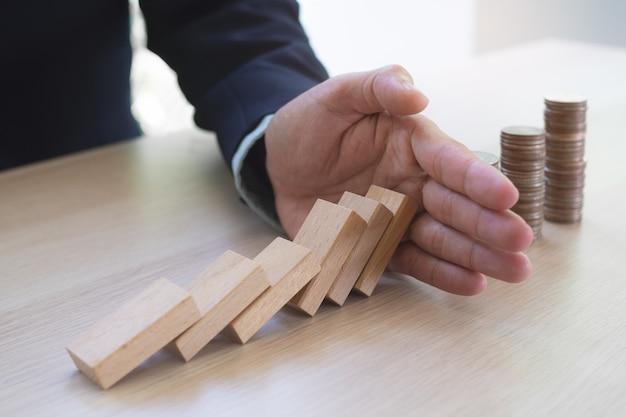 Finanza di protezione dal concetto di effetto domino. le mani fermano l'effetto domino prima di distruggere la pila di soldi. Foto Premium