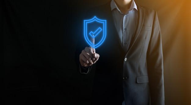 Computer di sicurezza di rete di protezione nelle mani di un uomo d'affari. affari, tecnologia, sicurezza informatica e concetto di internet - uomo d'affari premendo il pulsante scudo su schermi virtuali. protezione dati.