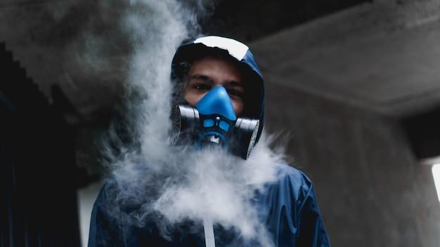 Mezza maschera del respiratore di protezione per gas tossici.l'uomo si prepara a indossare la protezione contro l'inquinamento atmosferico nell'industria chimica