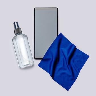 Protezione o igiene da virus o germi - pulizia o disinfezione del telefono cellulare con spray disinfettante disinfettante e panno