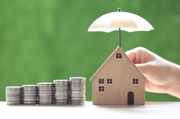 Protezione, pila di monete e modello di casa con la mano che tiene l'ombrello su sfondo verde naturale, assicurazione finanziaria e concetto di investimento sicuro