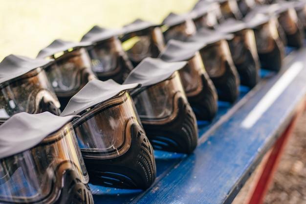 I caschi neri protettivi per il paintball giacciono su una mensola di legno pronti per un nuovo gioco, asciugando il casco all'esterno dopo il lavaggio