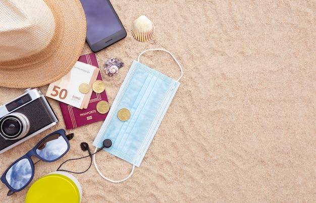 Maschera protettiva, un passaporto e qualche soldo, uno smartphone, un cappello, una macchina fotografica e occhiali da sole sulla spiaggia di sabbia. lay piatto