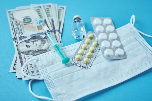 Maschera protettiva, articoli medici e banconote da un dollaro su sfondo blu.