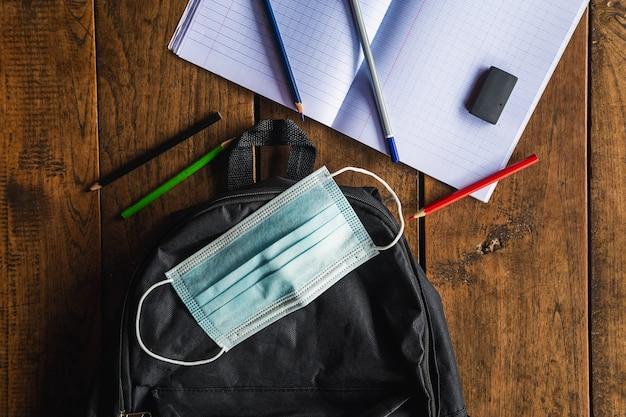 Maschera protettiva e borsa da scuola, materiale scolastico sul banco di scuola