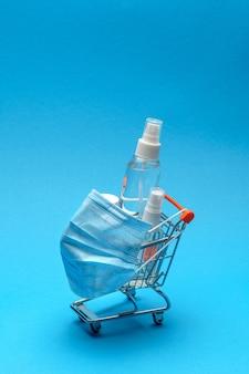 Maschere protettive e gel disinfettante disinfettante antibatterico in un piccolo carrello della spesa su sfondo blu con spazio di copia.