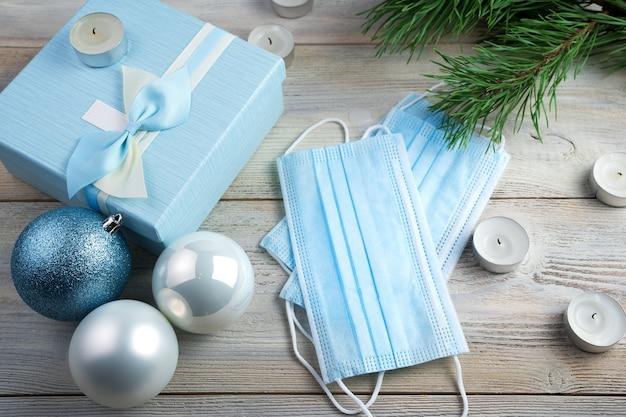 Maschere protettive su sfondo natalizio con candele