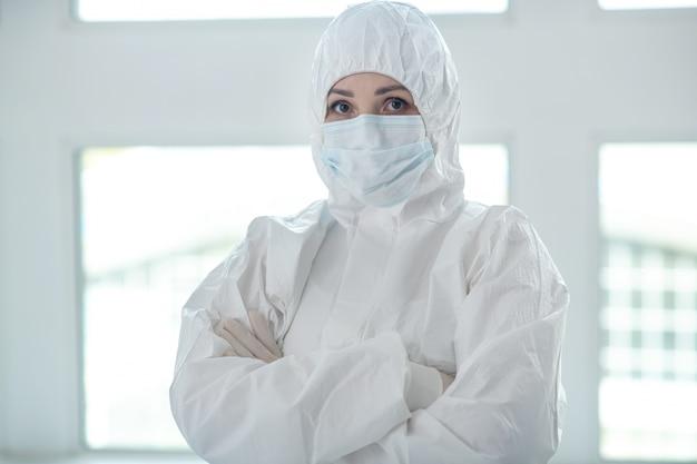 Misure protettive. lavoratore medico in abbigliamento protettivo e maschera medica in piedi con le braccia conserte