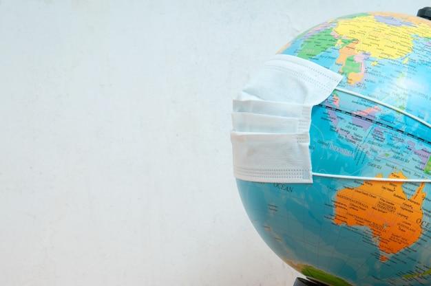 Maschera facciale protettiva medica sul globo del mondo