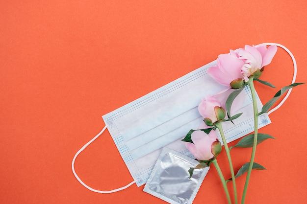 Maschera medica protettiva, peonia e preservativo. concetto di relazione d'amore nella nuova realtà normale.