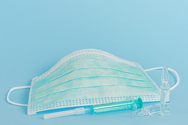 Maschera medica protettiva, fiale per vaccino e siringa
