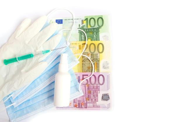 Maschere mediche protettive, vaccino con siringa e banconote in euro. copia spazio. il concetto di medicina costosa.