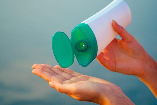 Crema solare protettiva sull'oceano nelle mani di una ragazza.