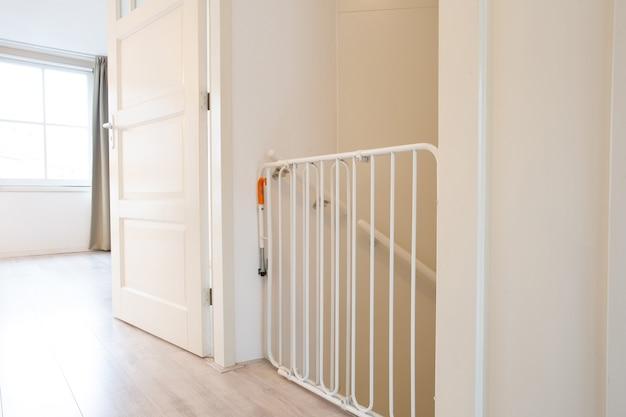 Cancello di sicurezza per bambini bianco protettivo nella nuova casa moderna della tromba delle scale del corridoio, recinzione per bambini in bella casa