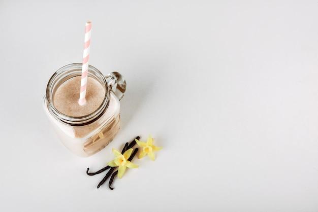 Cocktail proteico con vaniglia di latte in un barattolo di vetro con cannucce