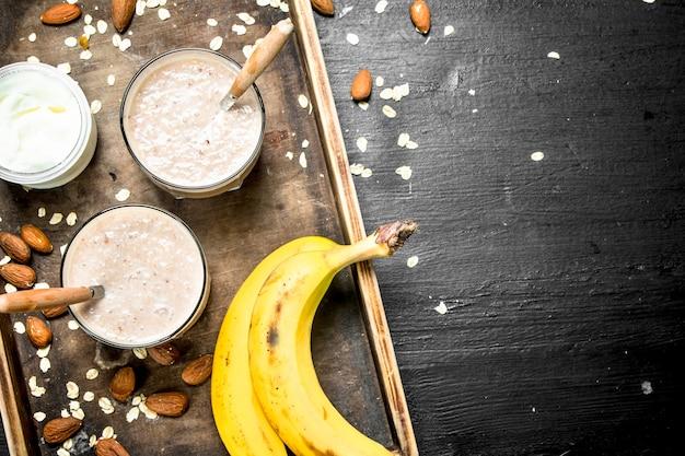 Frullato proteico con banana e noci. su sfondo nero.