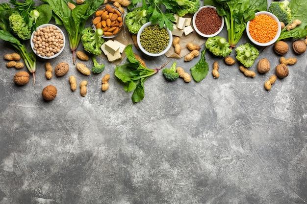 Proteine per vegetariani: tofu, verdure, noci, semi e legumi vista dall'alto su uno sfondo di cemento. concetto: cibo sano e pulito.