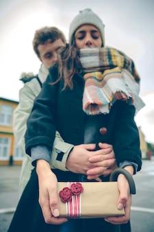 Ritratto di giovane bella donna che mostra scatola regalo nelle sue mani e il suo ragazzo che abbraccia da dietro all'aperto in una fredda giornata autunnale. amore e concetto di relazioni di coppia.