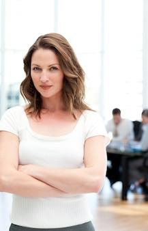 Imprenditrice orgogliosa in piedi davanti alla sua squadra mentre si lavora