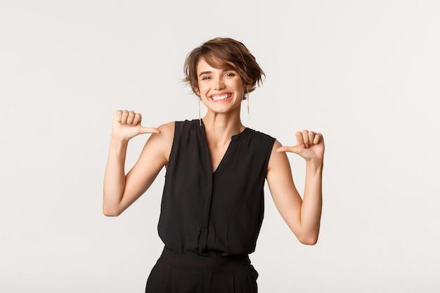 La giovane imprenditrice orgogliosa e felice raggiunge l'obiettivo, indicando se stessa con un sorriso soddisfatto, bianco.