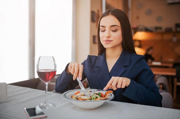 Orgogliosa e simpatica giovane donna sedersi a tavola e mangiare insalata con forchetta e coltello.