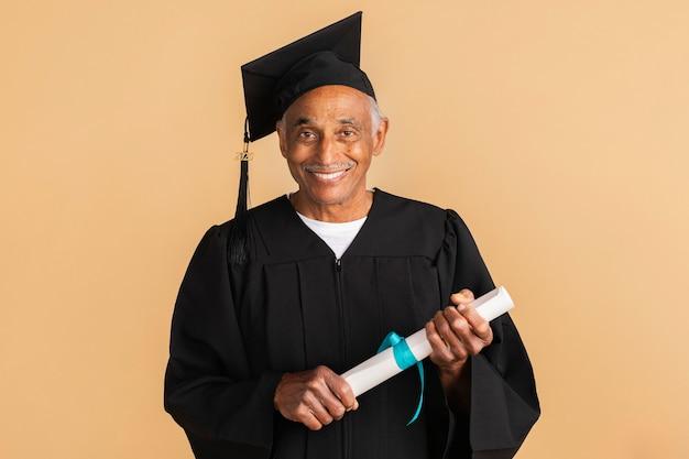 Orgoglioso uomo anziano in abito da laurea con in mano il diploma