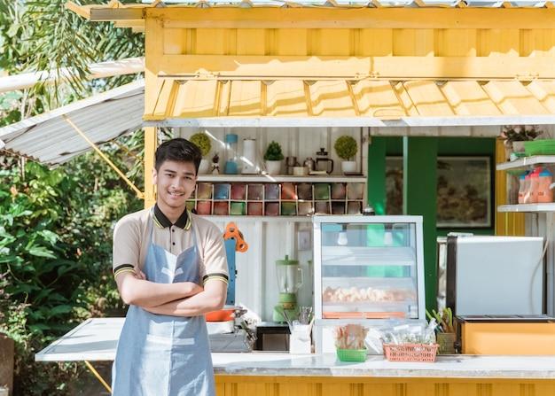 Orgoglioso giovane uomo asiatico proprietario di una piccola impresa nel suo negozio fatto di container per camion che vende cibo di strada