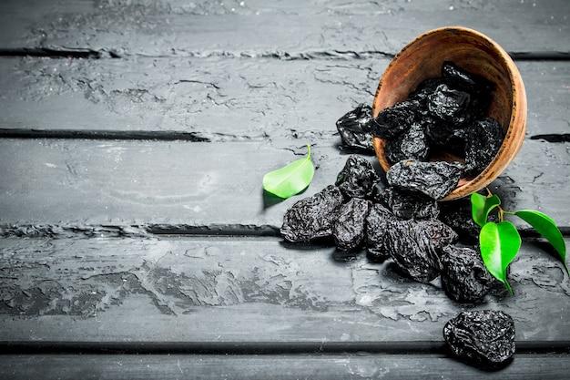 Le prugne secche in ciotola sul tavolo rustico nero.