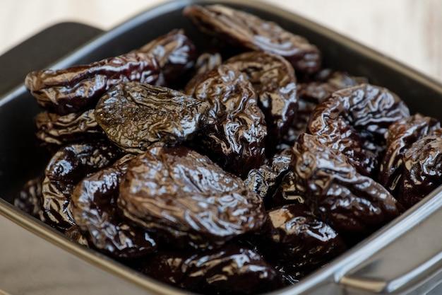 Gruppo di prugne in ciotola di legno. prugne secche in un piatto. piatto, cibo, nero