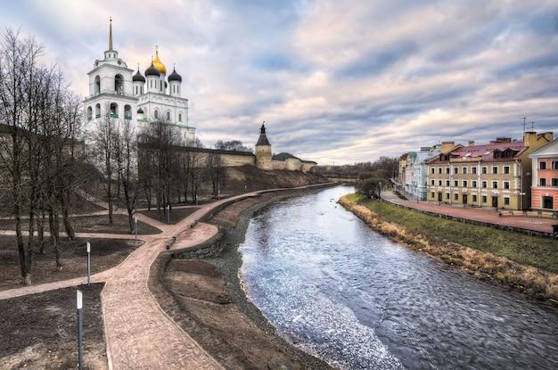 Cremlino di pskov sulle rive del fiume pskova e case sull'argine dorato in una nuvolosa giornata autunnale
