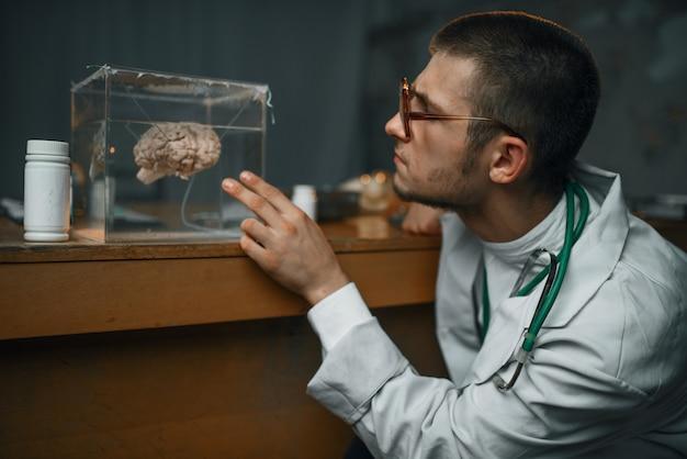 Lo psichiatra tiene un contenitore con il cervello umano