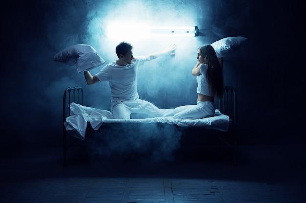 Psico uomo e donna litigano sui cuscini a letto, camera oscura .. persona psichedelica che ha problemi ogni notte, depressione e stress, tristezza, ospedale psichiatrico
