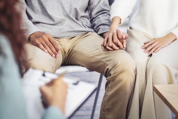 Il concetto di coppia di psicologi, i giovani amanti asiatici del primo piano stanno tenendo insieme la mano