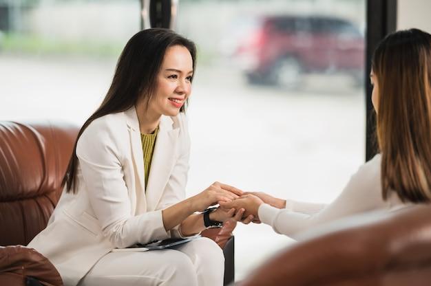 Psicologo che si tiene per mano e fornisce assistenza nella comprensione dei problemi di una paziente