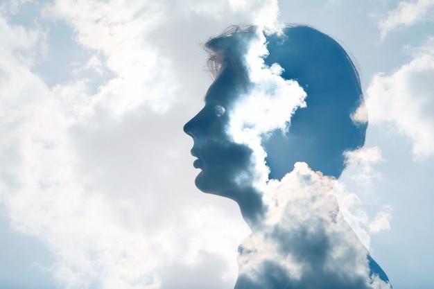 Psicologia e contemplazione della salute mentale dell'uomo e concetto di pressione atmosferica. esposizione multipla nuvole e sole sulla silhouette testa maschile.