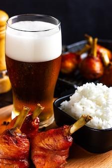 Menu da pub bicchiere di birra con cosce di pollo speziate al forno con schiuma e riso bollito caldo