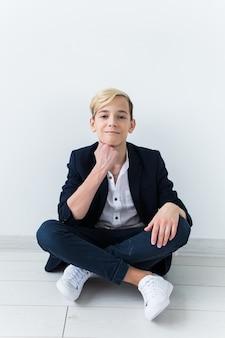 Concetto di pubertà - ritratto di adolescente su uno sfondo bianco.