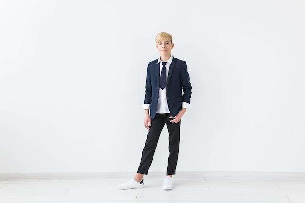 Concetto di pubertà - ritratto dell'adolescente su una superficie bianca con copyspace.