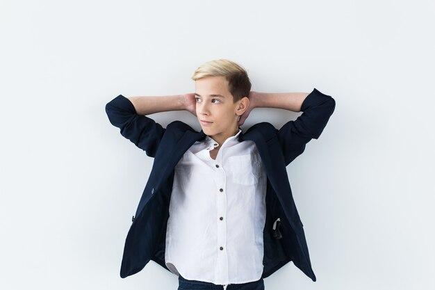 Concetto di pubertà - ritratto dell'adolescente su un muro bianco.