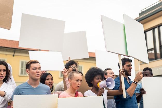Manifestazione pubblica sulla strada contro problemi sociali e diritti umani. gruppo di persone multietniche che protestano pubblicamente