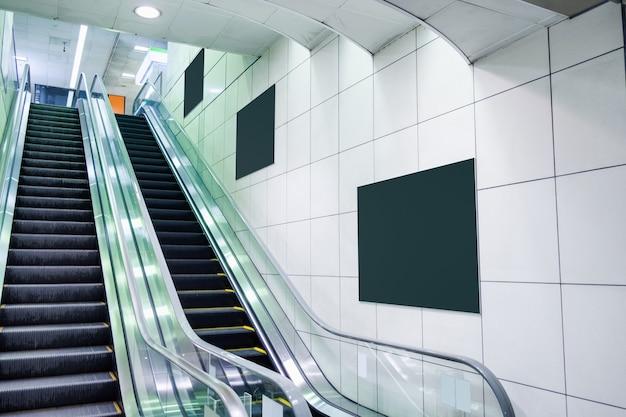 Scala mobile pubblica con tabellone per le affissioni in bianco sulla parete in metropolitana