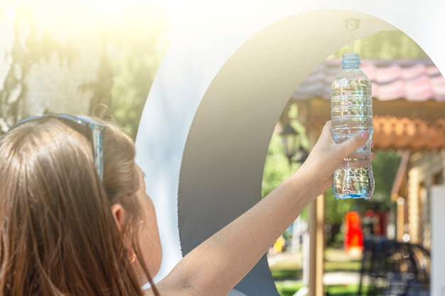Fontana pubblica di acqua potabile gratuita. donna che versa acqua nella bottiglia