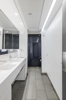 Interno pubblico o ufficio del bagno maschile con lavandini e bagno dal design moderno con grande specchio in bianco...