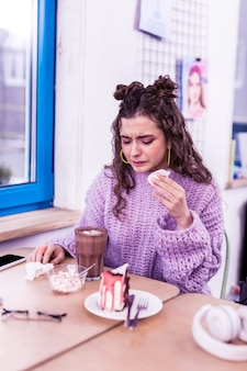 In luogo pubblico. adolescente malato infelice che si siede davanti al cacao e al pezzo di torta e che trasporta il tovagliolo sporco