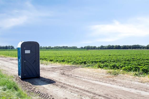 Toilette pubblica in plastica portatile sul campo agricolo del paesaggio contadino con cielo blu all'aperto