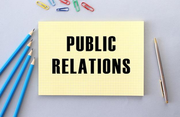 Relazioni pubbliche testo in taccuino sulla superficie grigia accanto a matite, penne e graffette.