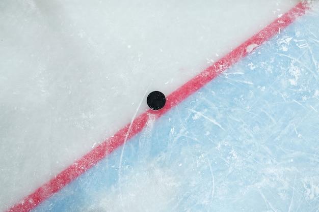 Puck sdraiato sulla linea rossa che divide lo spazio di gioco e la zona di rete sulla pista di pattinaggio per giocare a hockey che può essere utilizzato come sfondo