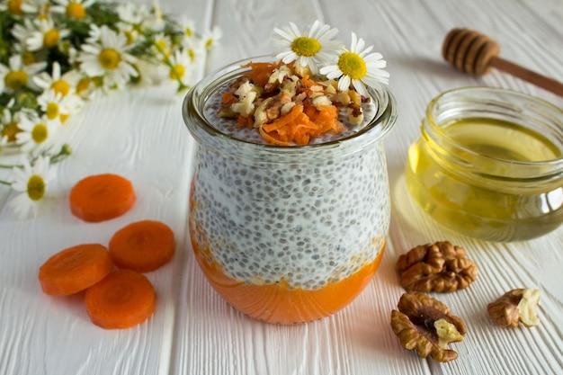 Budino con chia, carota, noci e miele sul legno bianco